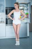 Young woman posing in front of an open fridge — Stock Photo