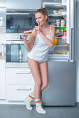 Naughty young woman stealing cake from the fridge — Stock Photo