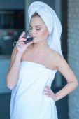Woman in towel drinking wine — Stock Photo