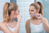 Young woman brushing her teeth in the mirror — Stock Photo
