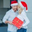 Woman kissing her husband on Christmas Day — Stock Photo #53917829
