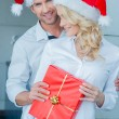 Happy couple celebrating Christmas in Santa hats — Stock Photo #54253037
