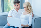 Concerned young couple using a laptop computer — Stock Photo