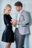 Couple in Trendy Attire Talking Something at Phone — Stock Photo
