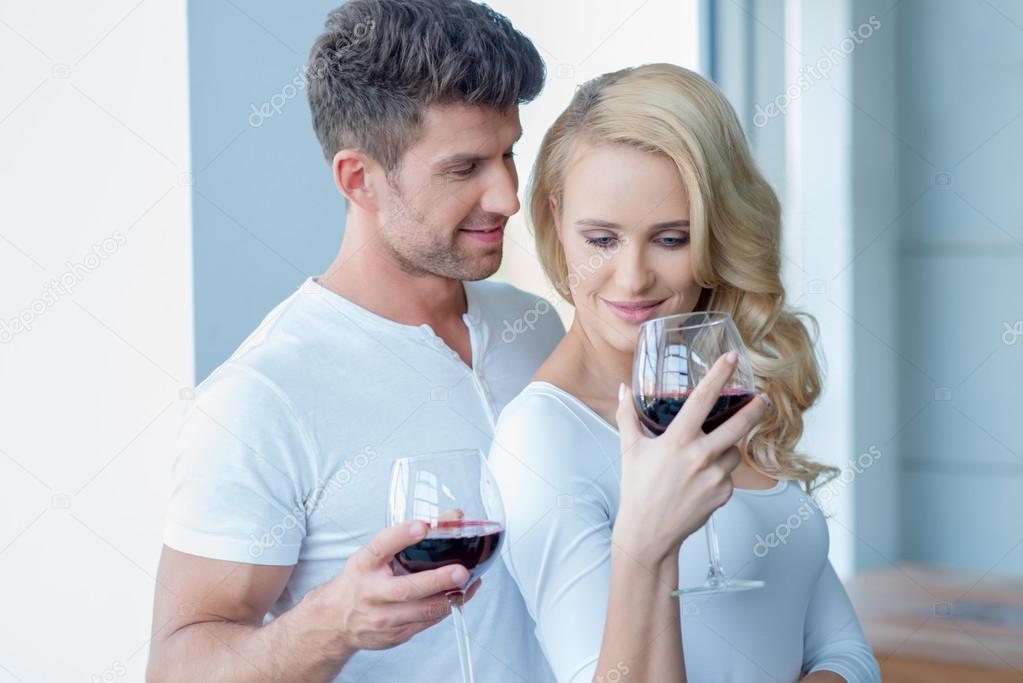 casal feliz bebendo vinho tinto para comemorar. Black Bedroom Furniture Sets. Home Design Ideas