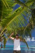 Man Standing Beneath Palm Tree on Tropical Beach — Foto Stock