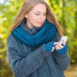Young woman using a mobile outdoors in autumn — Stock Photo #54926025
