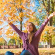 Happy young woman rejoicing in an autumn park — Stock Photo #54927241