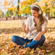 Young woman listening to music in an autumn park — Stock Photo #54927543
