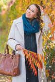 Stylish young woman picking autumn leaves — Stock Photo