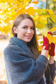 Smiling woman gathering autumn leaves — Stock Photo