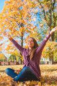 Happy young woman rejoicing in an autumn park — Stock Photo
