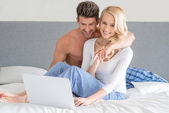 Young couple relaxing in bed using a laptop — Stock Photo