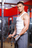 Athletic young man working out in a gym — Stock Photo