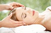 Woman relaxing at spa having a facial — Stock Photo