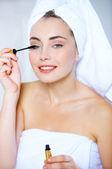 Young woman applying mascara to her eyelashes — Stock Photo