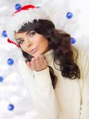Young woman in a Santa Hat blowing a kiss — Stock Photo