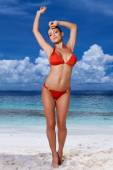 Sexy young woman in a red bikini at the beach — Stock Photo