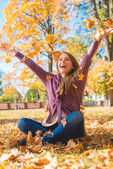 Happy Woman Sitting on Ground Playing Dry Leaves — Stock Photo