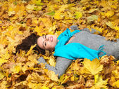 Beautiful lady lying in dry leaves — Stock Photo
