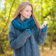 Young woman using a mobile outdoors in autumn — Stock Photo #55623893