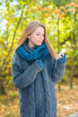 Young woman using a mobile outdoors in autumn — Stock Photo