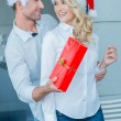 Playful man giving his wife a Christmas gift — Stock Photo #55741939
