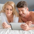 Sexy Young Couple Watching Movie on White Tablet — Stock Photo #55742145