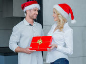 Pretty woman giving her husband a Christmas gift — Stock Photo