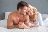 Happy attractive couple relaxing on their bed — Stock Photo