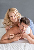 Pretty Woman Lying Over Handsome Partner on Bed — Stock Photo