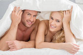 Young couple peeking out from under the bedclothes — Stock Photo