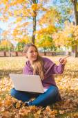 Happy Woman Sitting on Dried Leaves with Laptop — Stock Photo