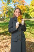 Smiling Young Woman in Gray Coat Holding Leaves — Foto de Stock