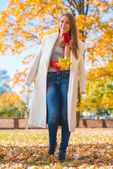 Pretty Woman in Big White Coat Holding Leaves — Stock Photo