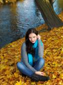 Woman in Autumn Outfit Sitting on Dry Leaves — Stockfoto