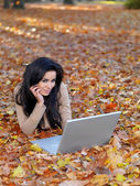 Pretty Smiling Woman Lying on Ground with Laptop — Stock Photo