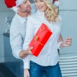 Husband surprising his wife with a Christmas gift — Stock Photo #55970111