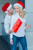 Husband surprising his wife with a Christmas gift — Stock Photo