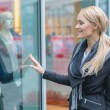 Happy young woman window shopping — Stock Photo #56097465