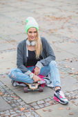 Woman in Trendy Attire Sitting Over Skateboard — Stock Photo