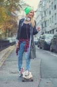 Cute young urban woman using a skate board — Stok fotoğraf