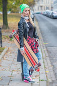 Trendy young woman carrying a skate board — Stok fotoğraf
