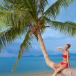 Attractive woman sunbathing on a palm tree — Stock Photo #56192997