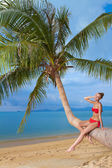 Attractive woman sunbathing on a palm tree — Stok fotoğraf