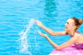 Happy woman splashing water in a swimming pool — Stockfoto