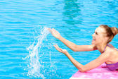 Happy woman splashing water in a swimming pool — Foto de Stock