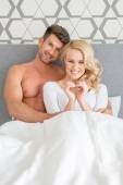 Attractive couple sitting together in bed — Стоковое фото
