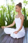 Young woman practicing yoga sitting meditating — Стоковое фото