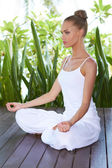 Young woman practicing yoga sitting meditating — Stok fotoğraf